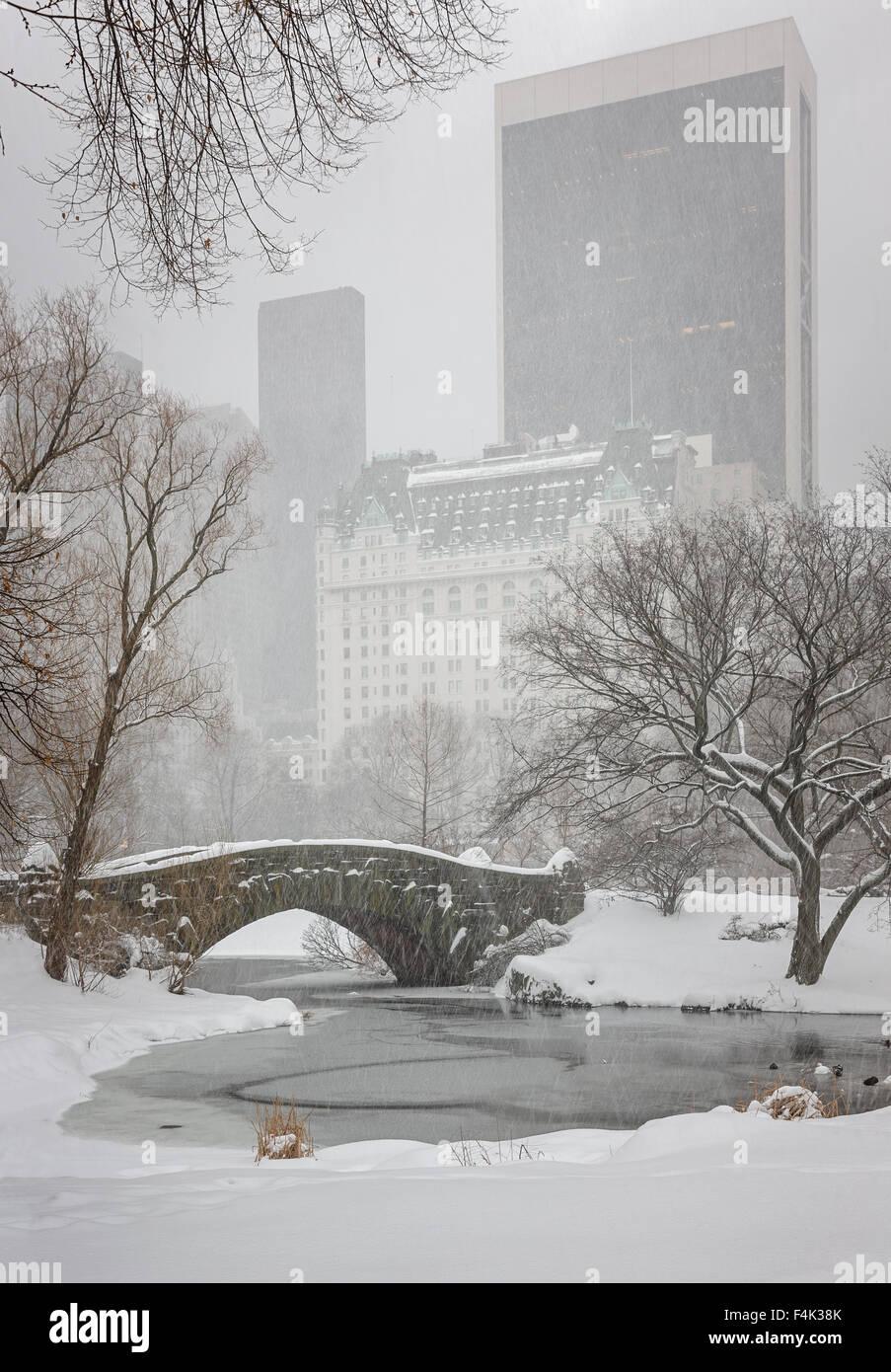 Schneefall am Central Park-Gapstow-Brücke und den Teich. Ruhigen Winterlandschaft mit Blick auf die Wolkenkratzer Stockbild