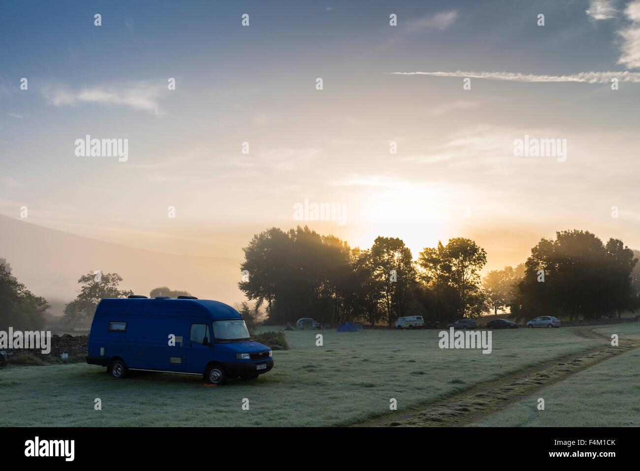 Der aufgehenden Sonne durch den Nebel an einem frostigen Morgen im hohen Laning Brennen auf dem Bauernhof Campingplatz Stockbild