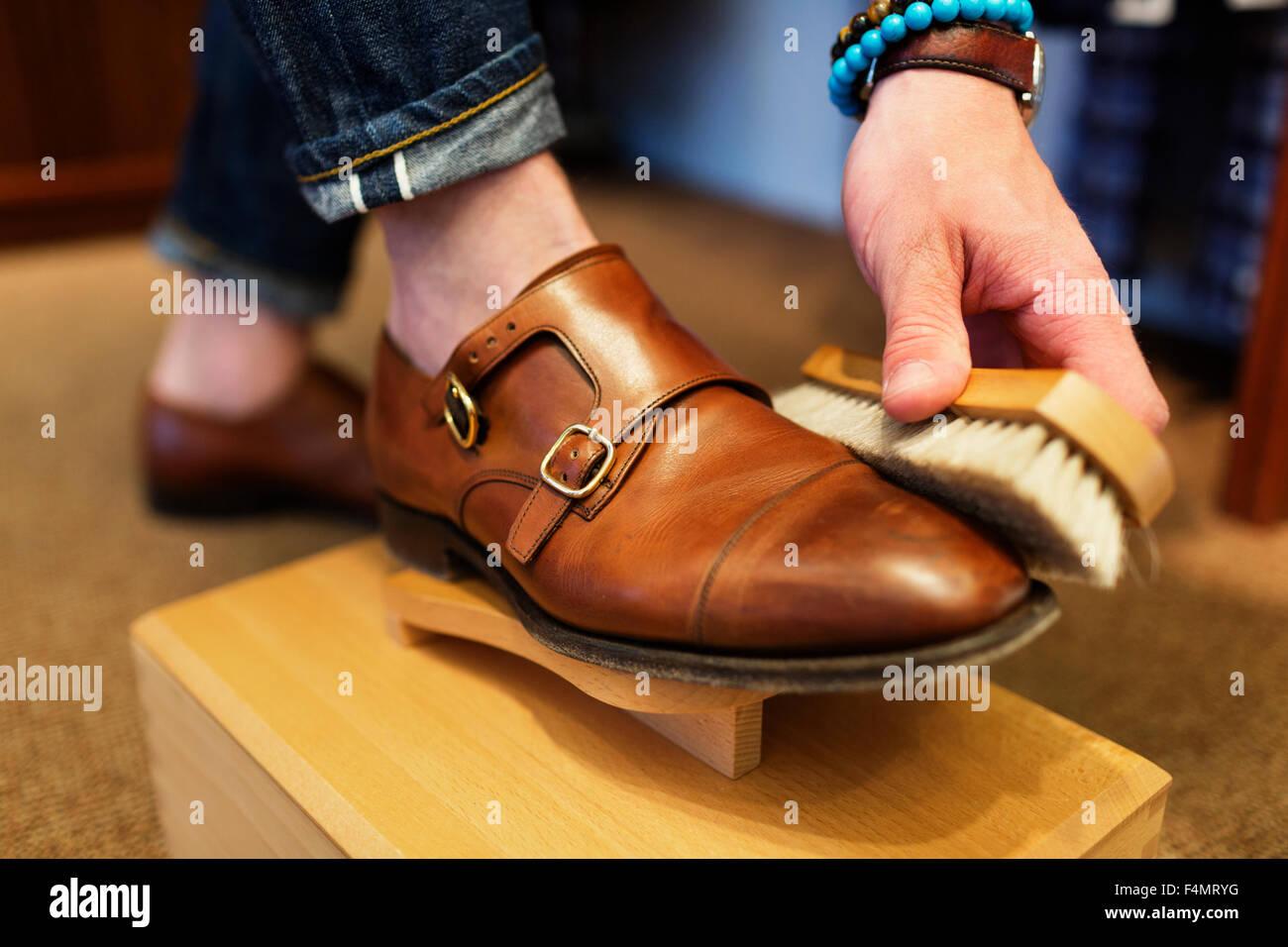 Niedrige Teil der Kunden mit Pinsel auf Schuh im store Stockfoto