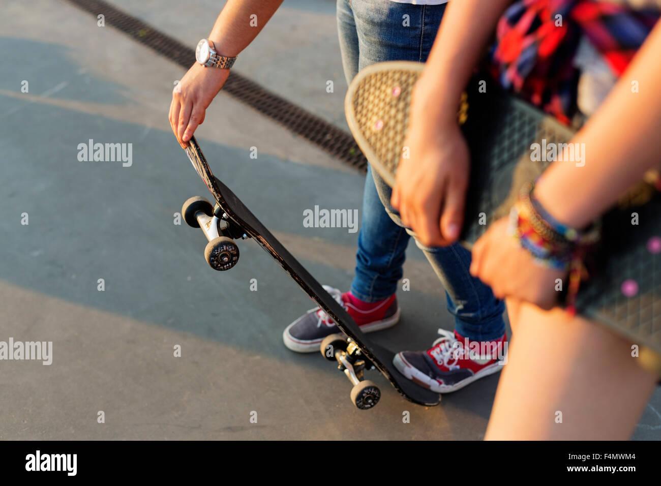Mittelteil der Mädchen im Teenageralter mit Skateboards im Skatepark Stockbild