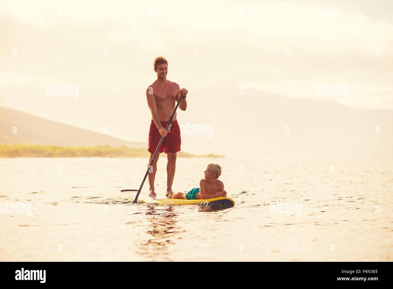 Vater und Sohn aufstehen paddeln bei Sonnenaufgang, Sommer Spaß outdoor-Lifestyle Stockbild