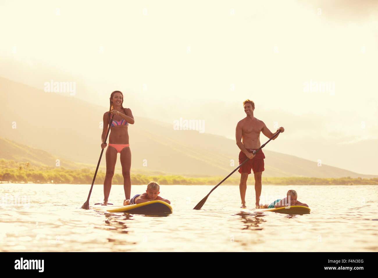 Familie Stand-up Paddeln bei Sonnenaufgang, Sommer Spaß outdoor-Lifestyle Stockbild