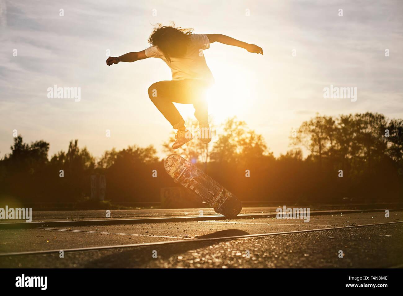 Junger Mann auf Skateboard bei Gegenlicht Stockbild