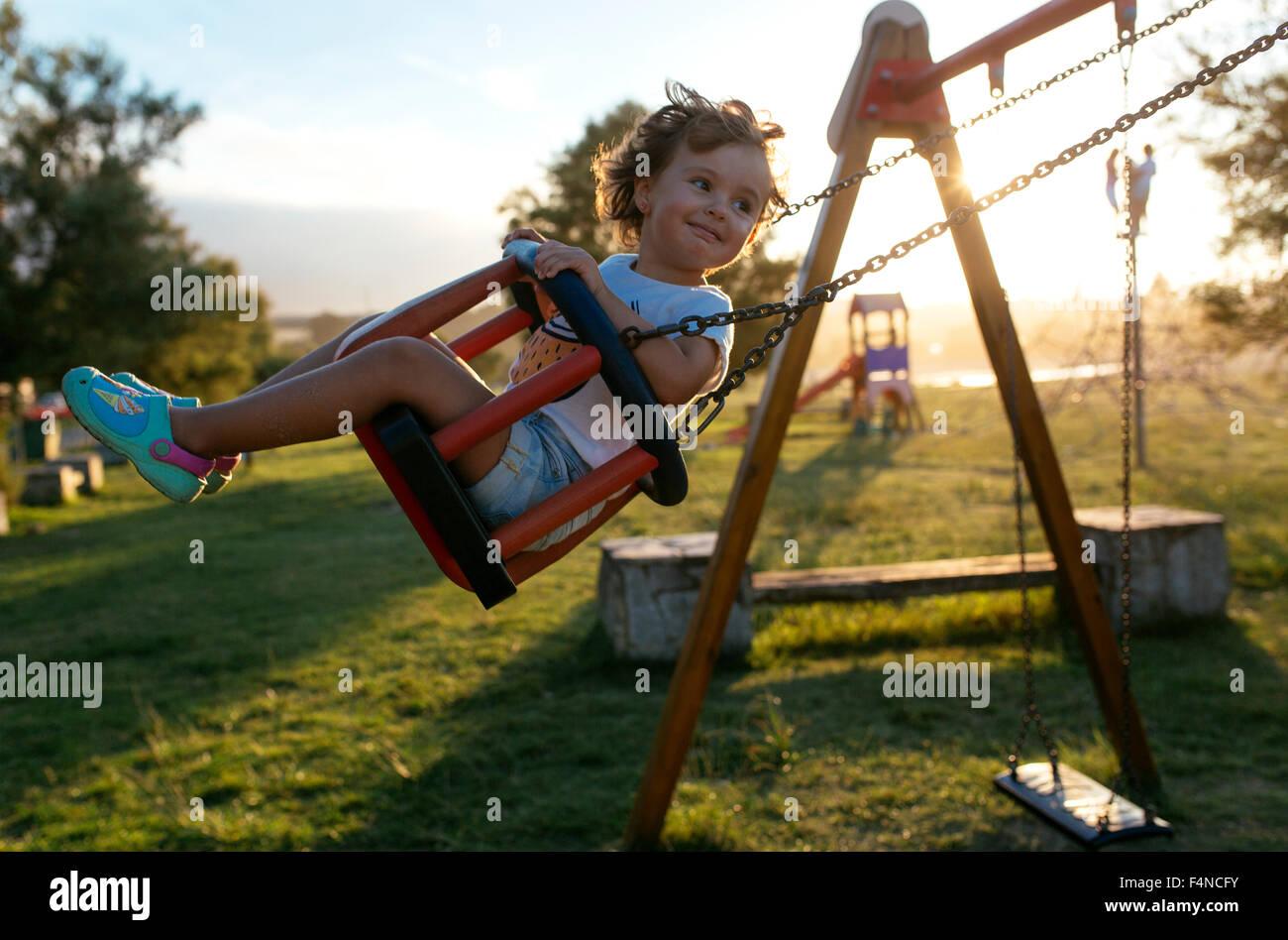 Porträt von glückliches kleines Mädchen auf einer Schaukel im Gegenlicht Stockbild
