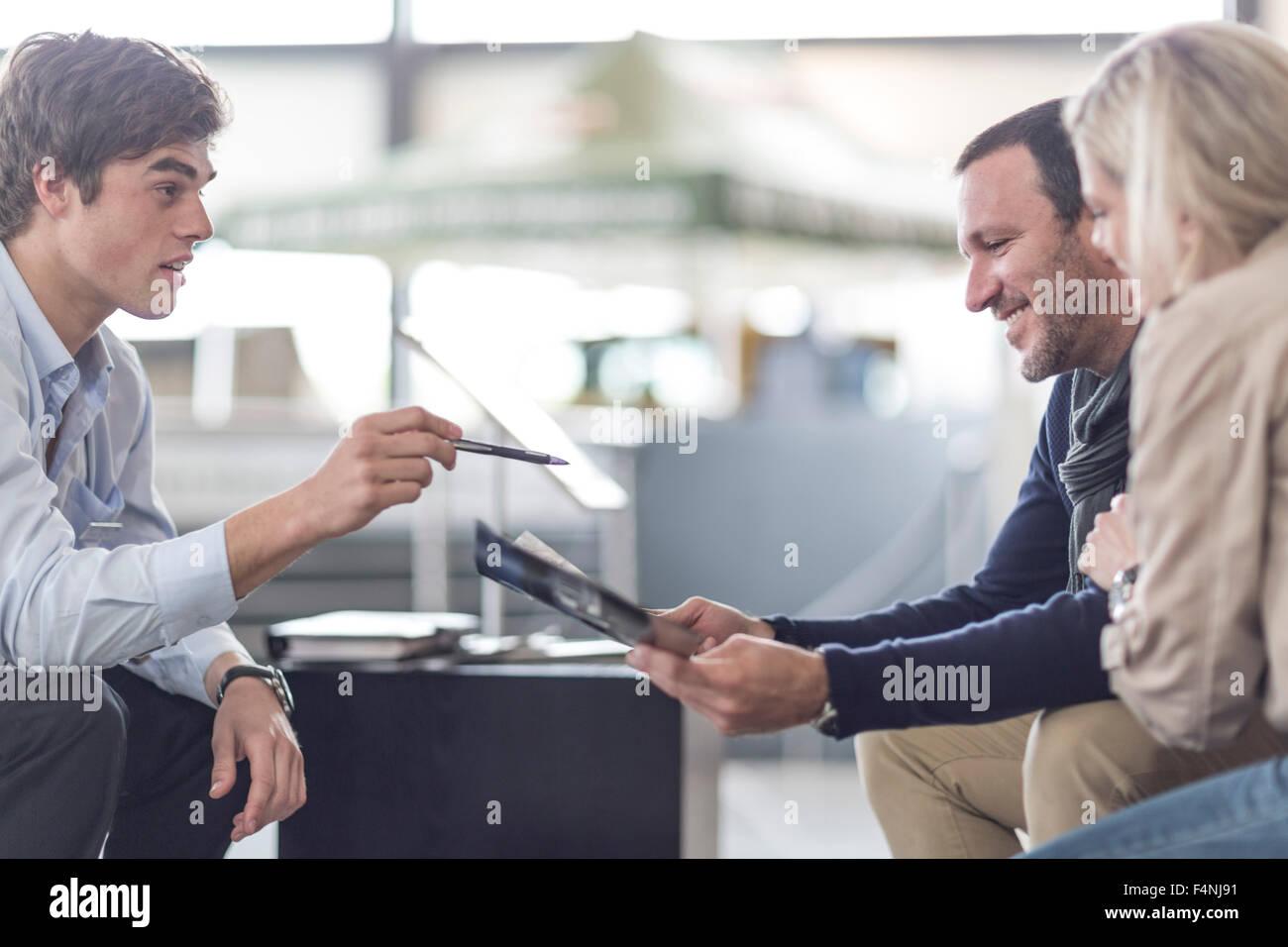 Kfz-Händler im Gespräch mit paar Stockbild
