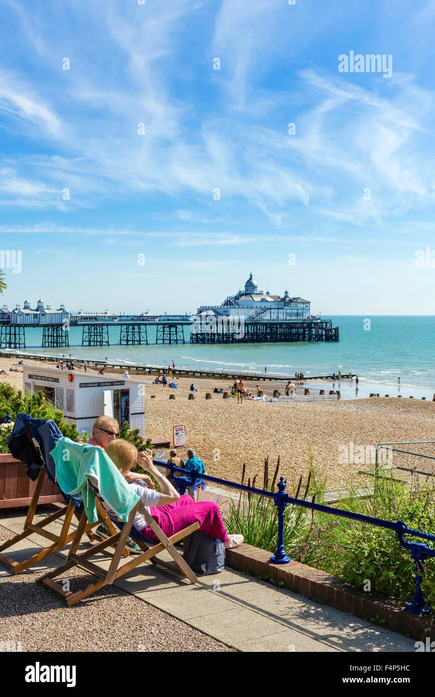 Zwei ältere Frauen sitzen auf der Promenade mit Strand und Pier hinter Grand Parade, Eastbourne, East Sussex, Stockbild