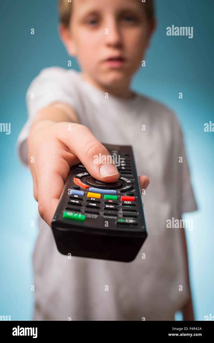 Eine gelangweilte junge Senderwechsel über eine TV-Fernbedienung Stockbild
