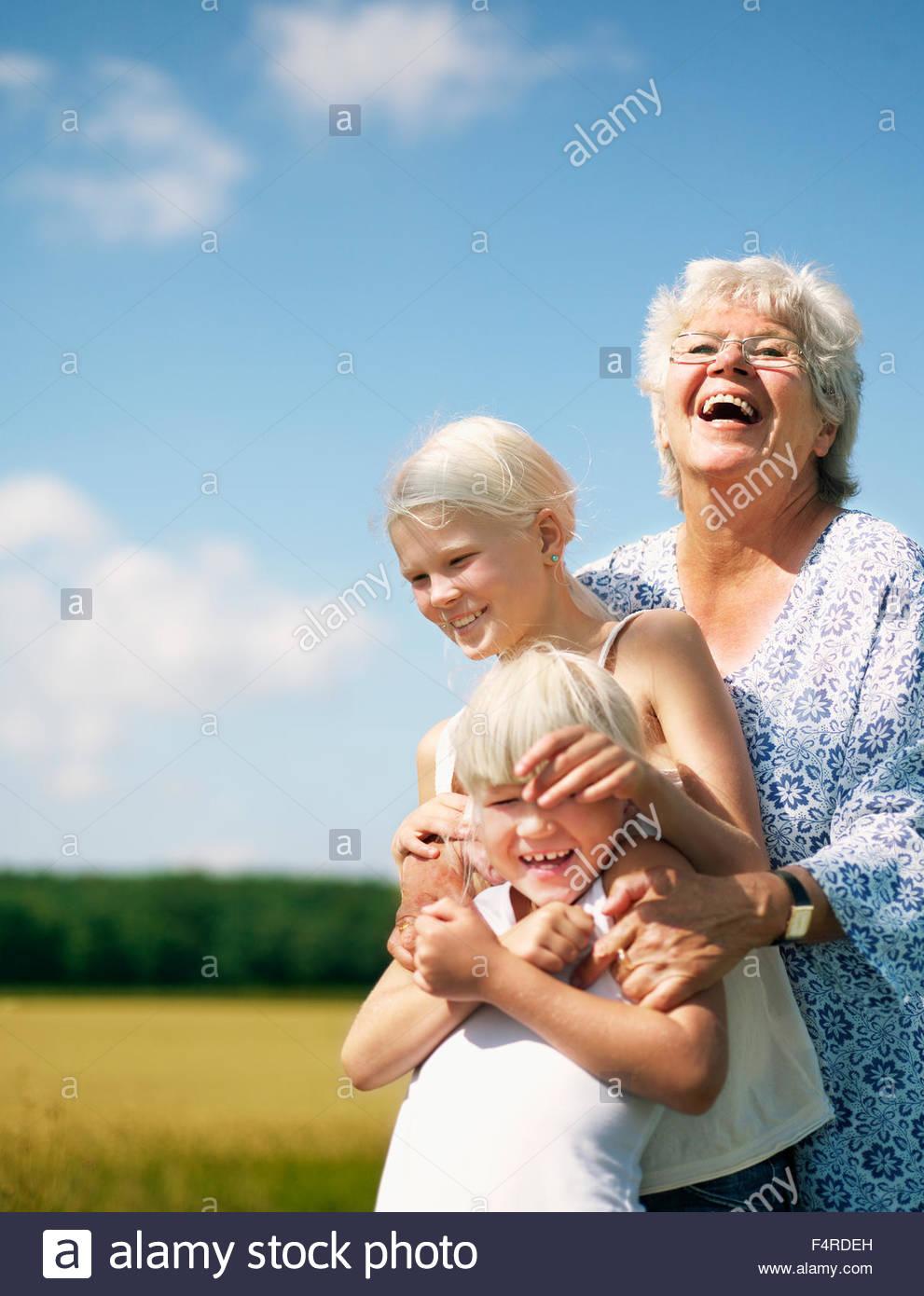 Outdoor-Porträt der Großmutter mit zwei Enkelinnen (6-7, 12-13) Stockbild
