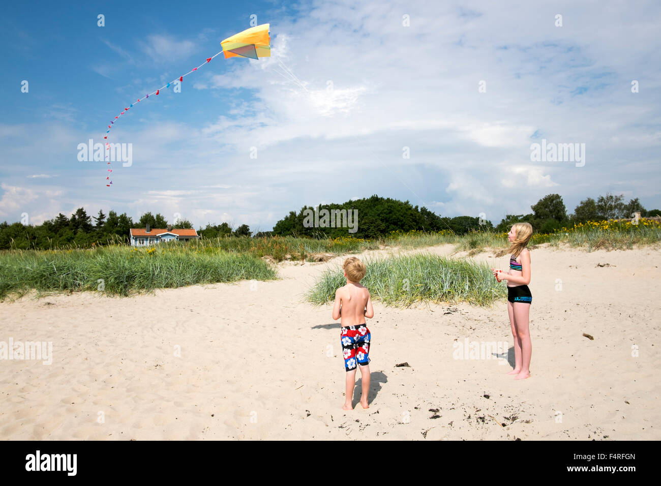 Schweden, Skane, Vejbystrand, junge (6-7) und Mädchen (10-11) fliegende Drachen Stockbild