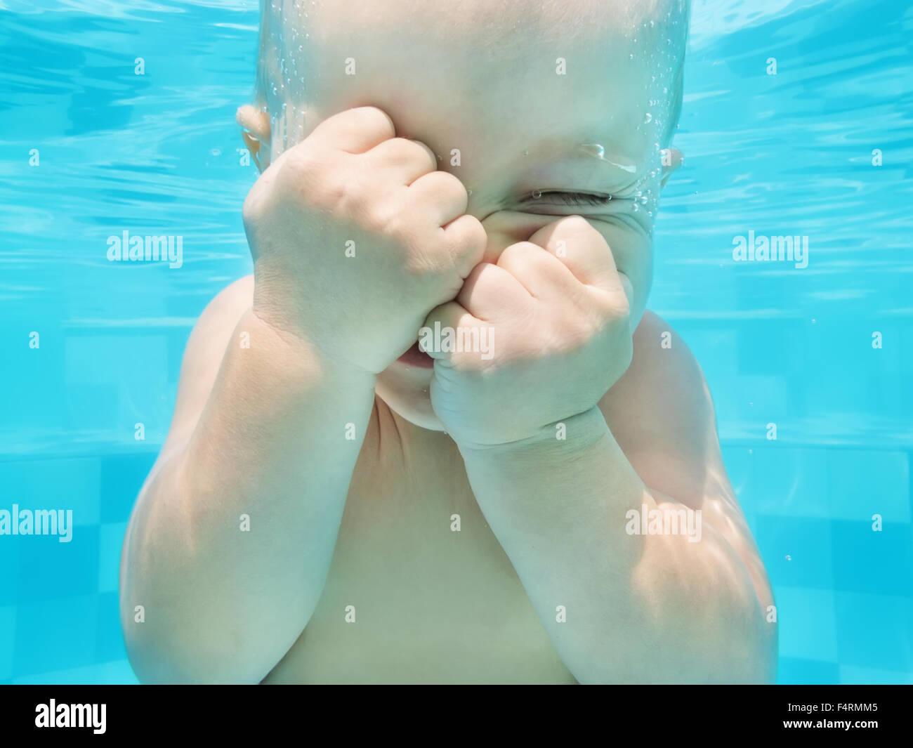 Lustiges Gesicht Porträt des kleinen Jungen mit einer Lektion in blauen Pool - schwimmen und Tauchen Unterwasser Stockbild