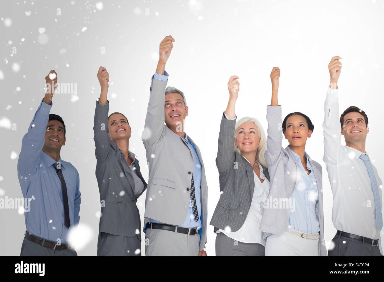 Zusammengesetztes Bild des Lächelns Geschäftsleute Hände erhebend Stockfoto