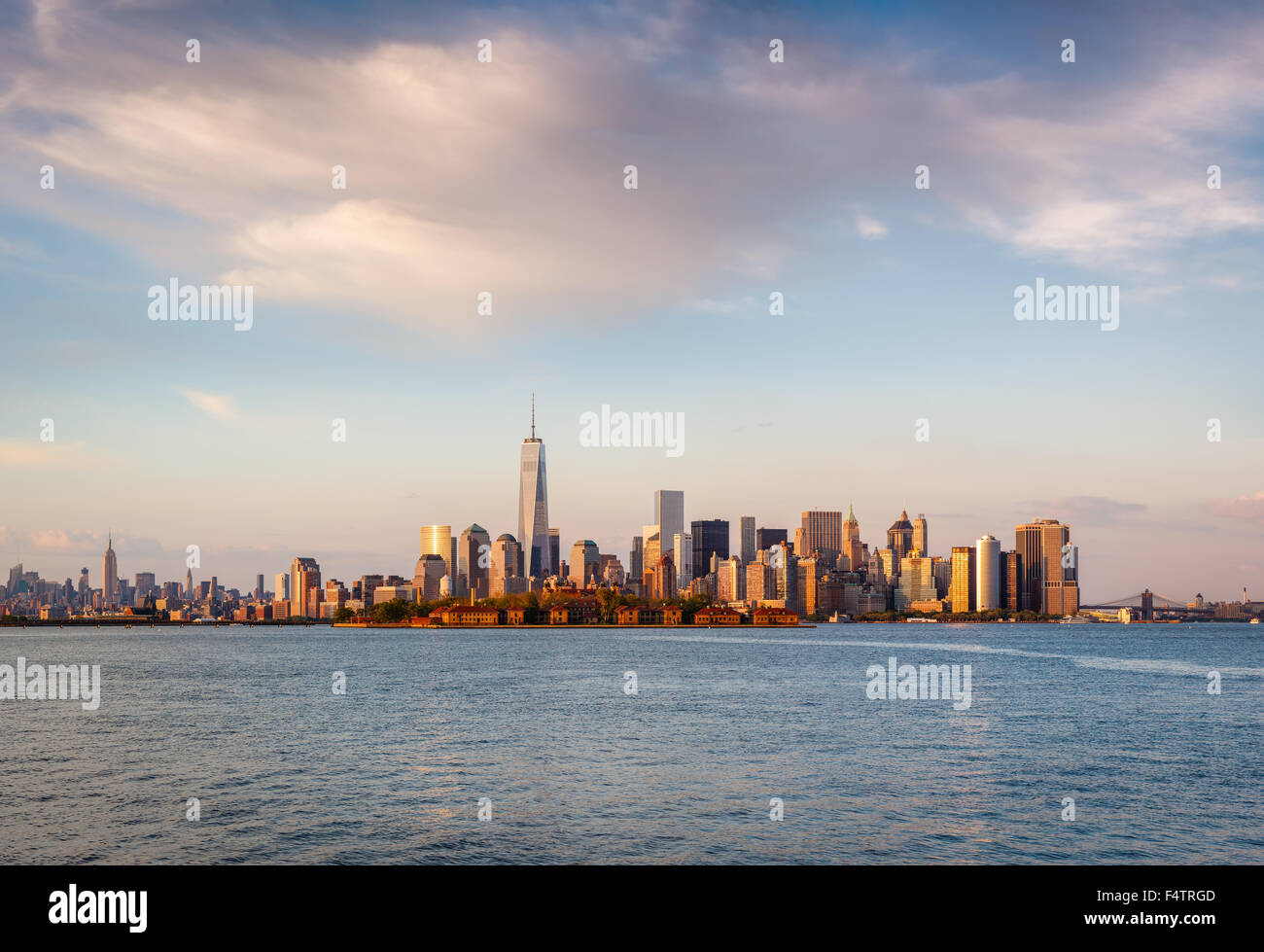 New Yorker Wolkenkratzer und Lower Manhattan Financial District im Abendlicht mit Battery Park und Ellis Island. Stockbild