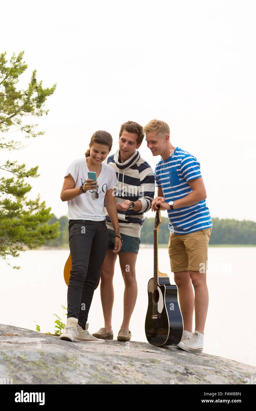 Freunde, zwei junge Männer und Mädchen (12-13) stehen am Meer und mit Blick auf smartphone Stockbild