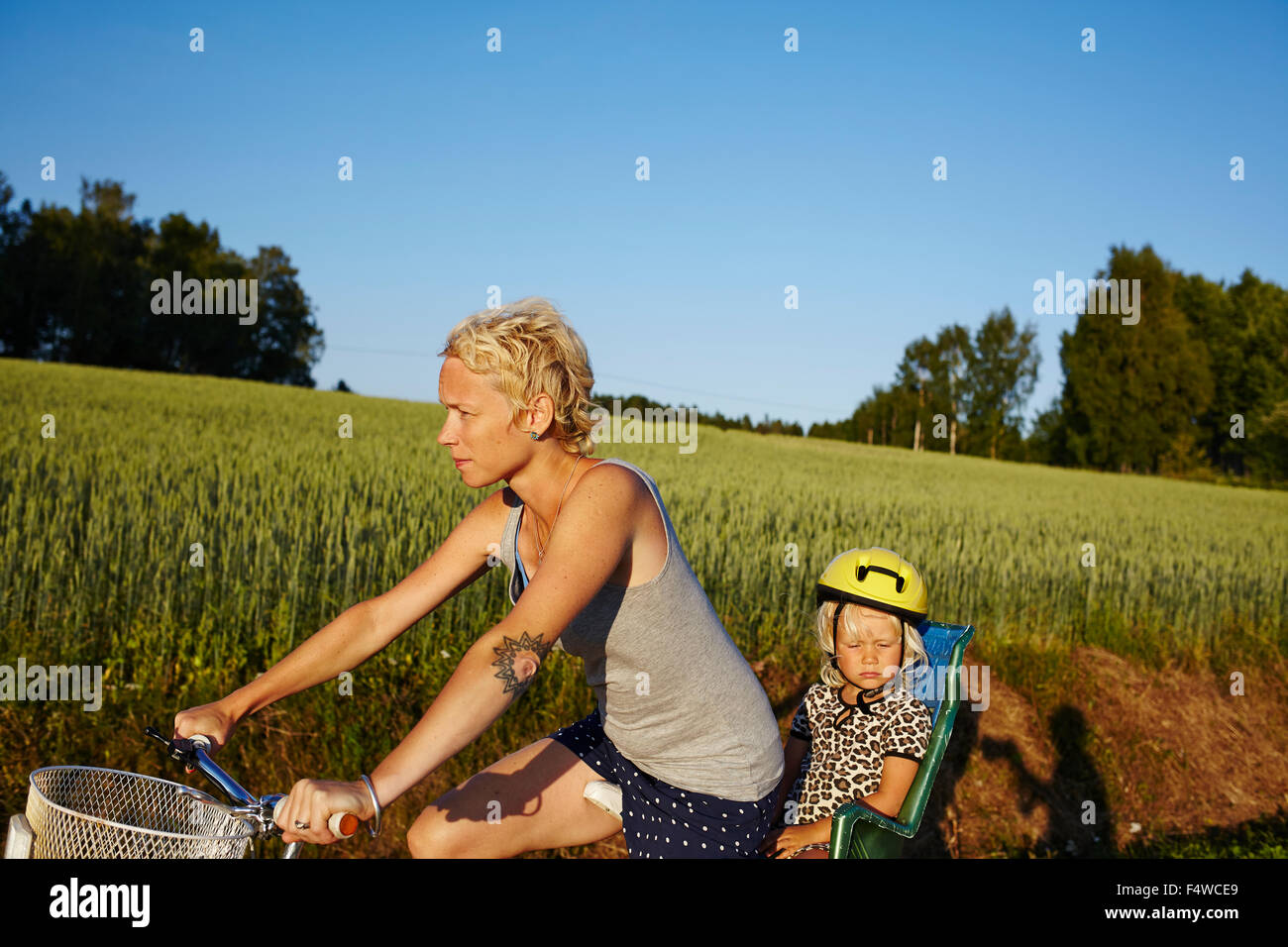 Frau mit Tochter (4-5) Reiten Fahrrad Stockbild