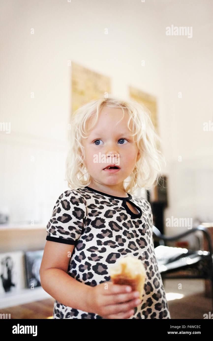 Porträt des blonden Mädchens (4-5) süße Brötchen essen Stockbild