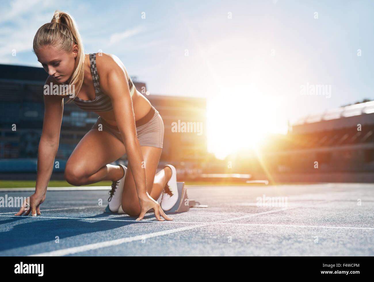 Junge Sportlerin in Ausgangsposition bereit, ein Rennen zu starten. Weibliche Sprinter bereit für sportliche Stockbild
