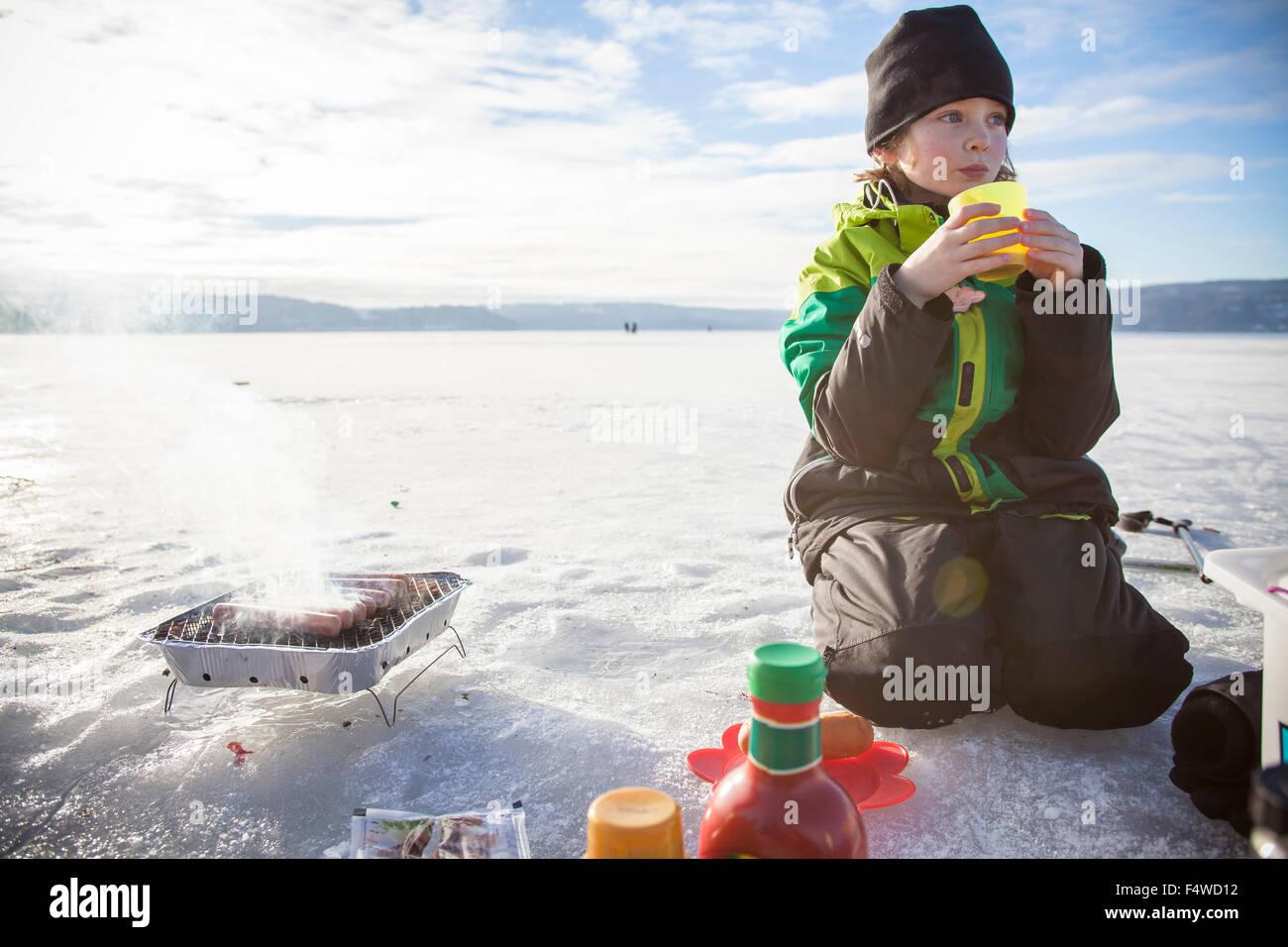 Jungen (8-9) trinken Tee im freien Stockbild