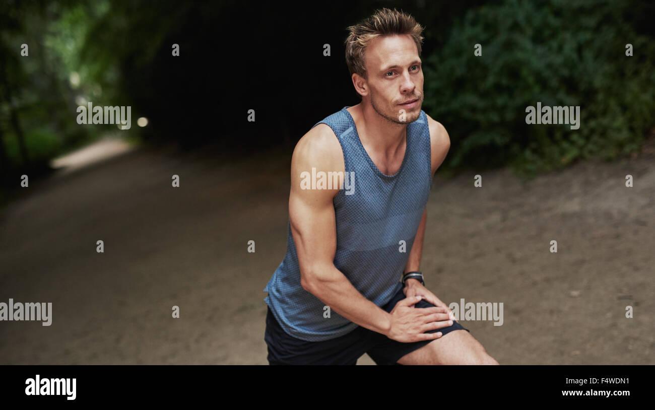 Sportlich gut aussehender Mann Aufwärmen vor seinem Training oder Joggen, stretching Übungen im Freien Stockbild