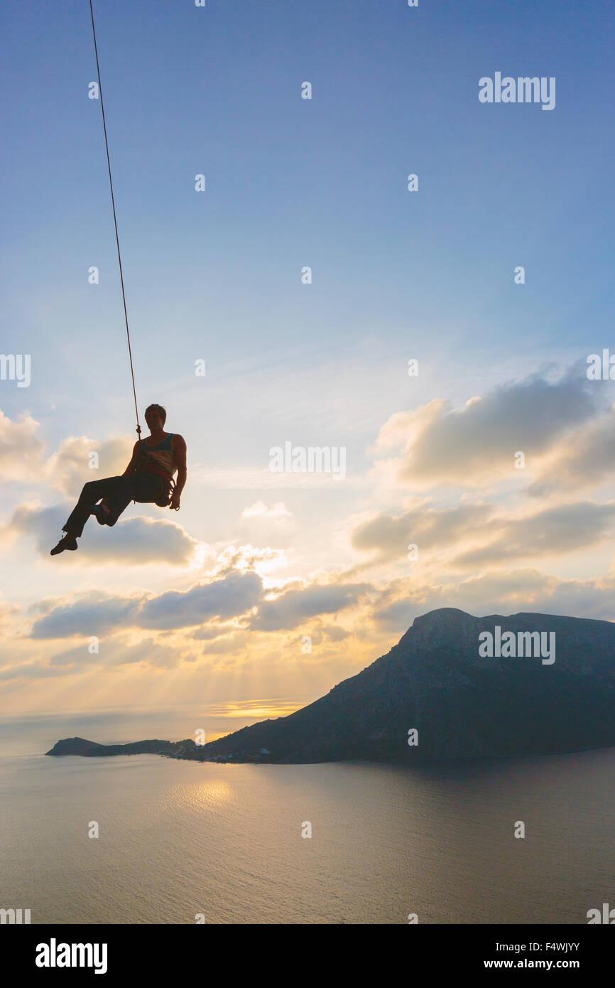 Griechenland, Dodekanes, Kalymnos, Mann Übergabe Klettertau gegen Himmel Stockbild