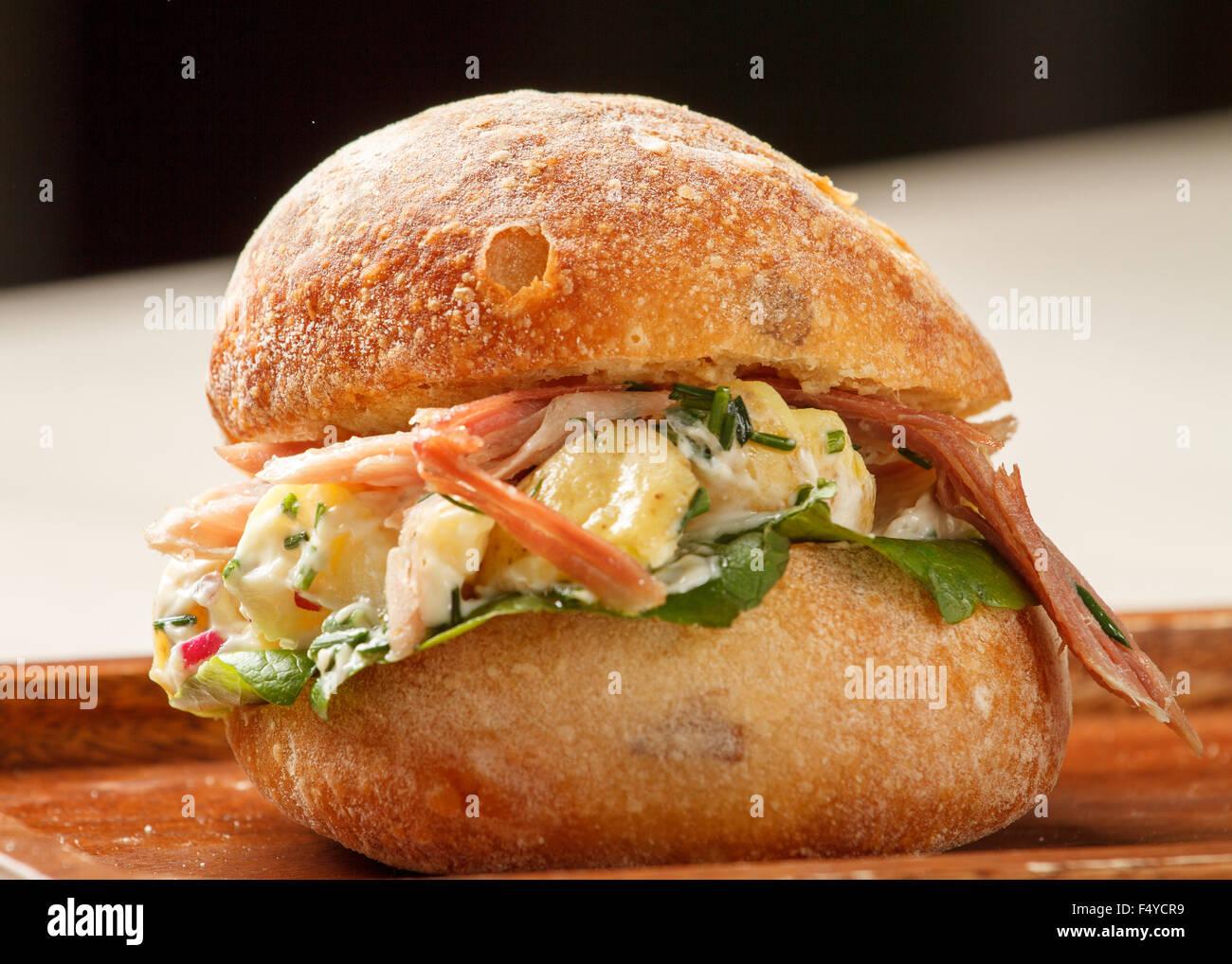 Sandwich in einem Brötchen mit Speck und Kartoffelsalat gemacht Stockbild