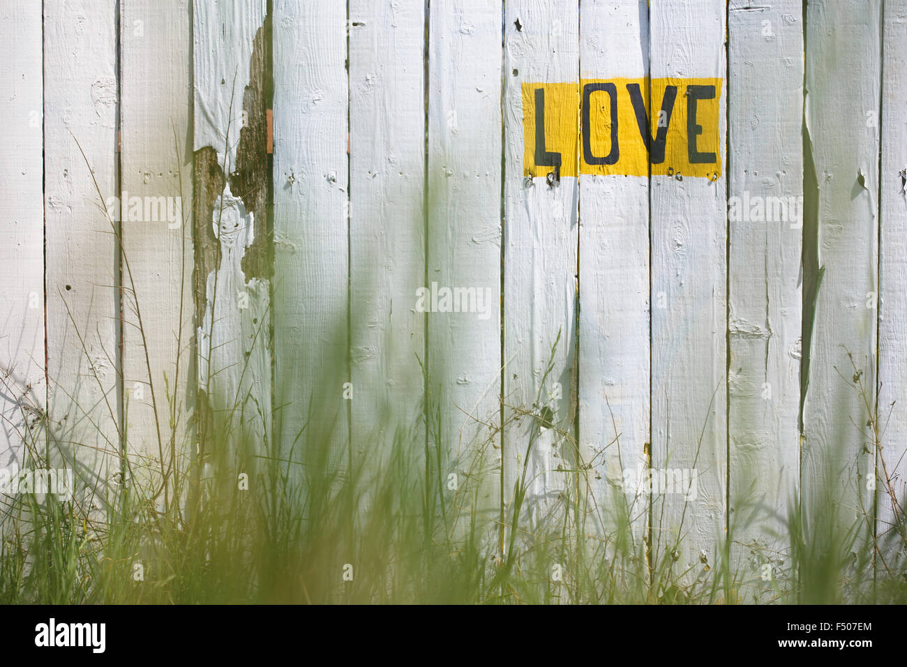 """Das Wort """"LOVE"""" geschrieben auf einem weiß getünchten Zaun Stockbild"""