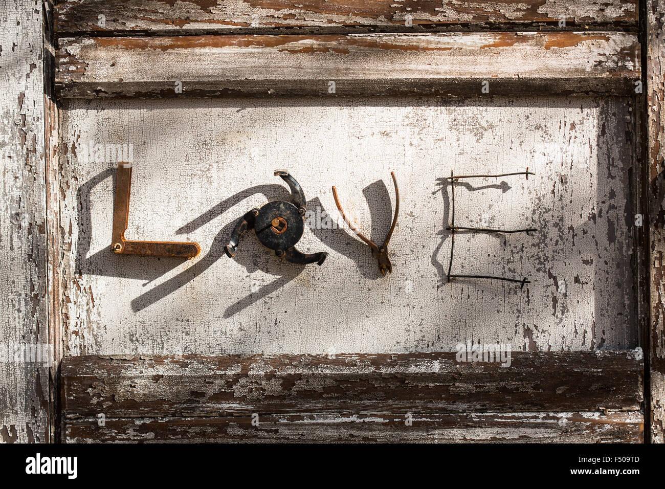 """Das Wort """"Liebe"""" ausgeschrieben, mit Metall-Teile auf einem hölzernen Hintergrund Stockbild"""