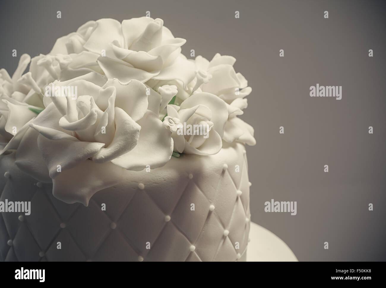 Details zu einer Hochzeitstorte, Dekoration mit weißen Fondant auf weißem Hintergrund. Stockbild