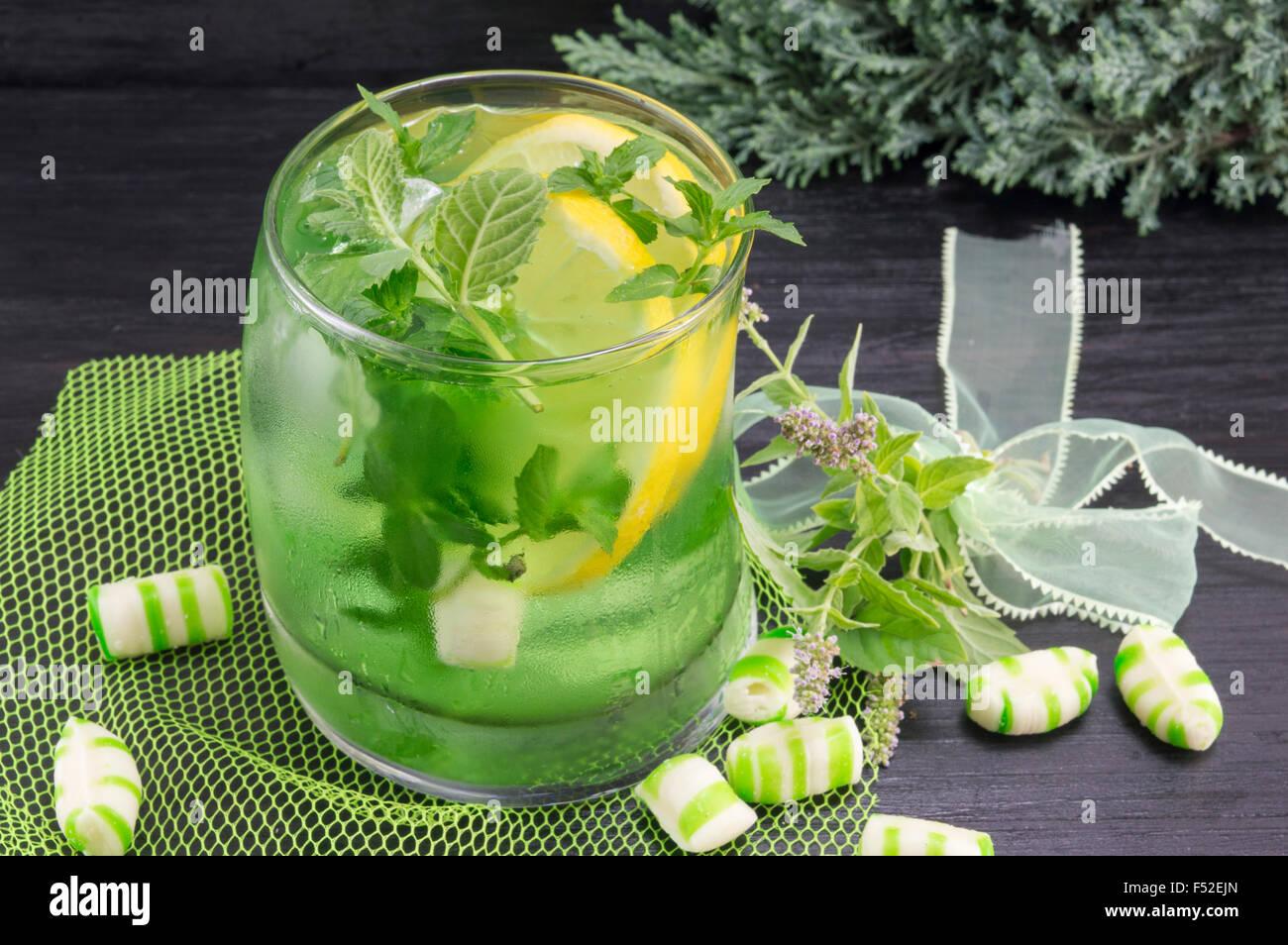 Hausgemachtes Mojito cocktail in einem krummen Glas mit Minze bonbons Stockbild