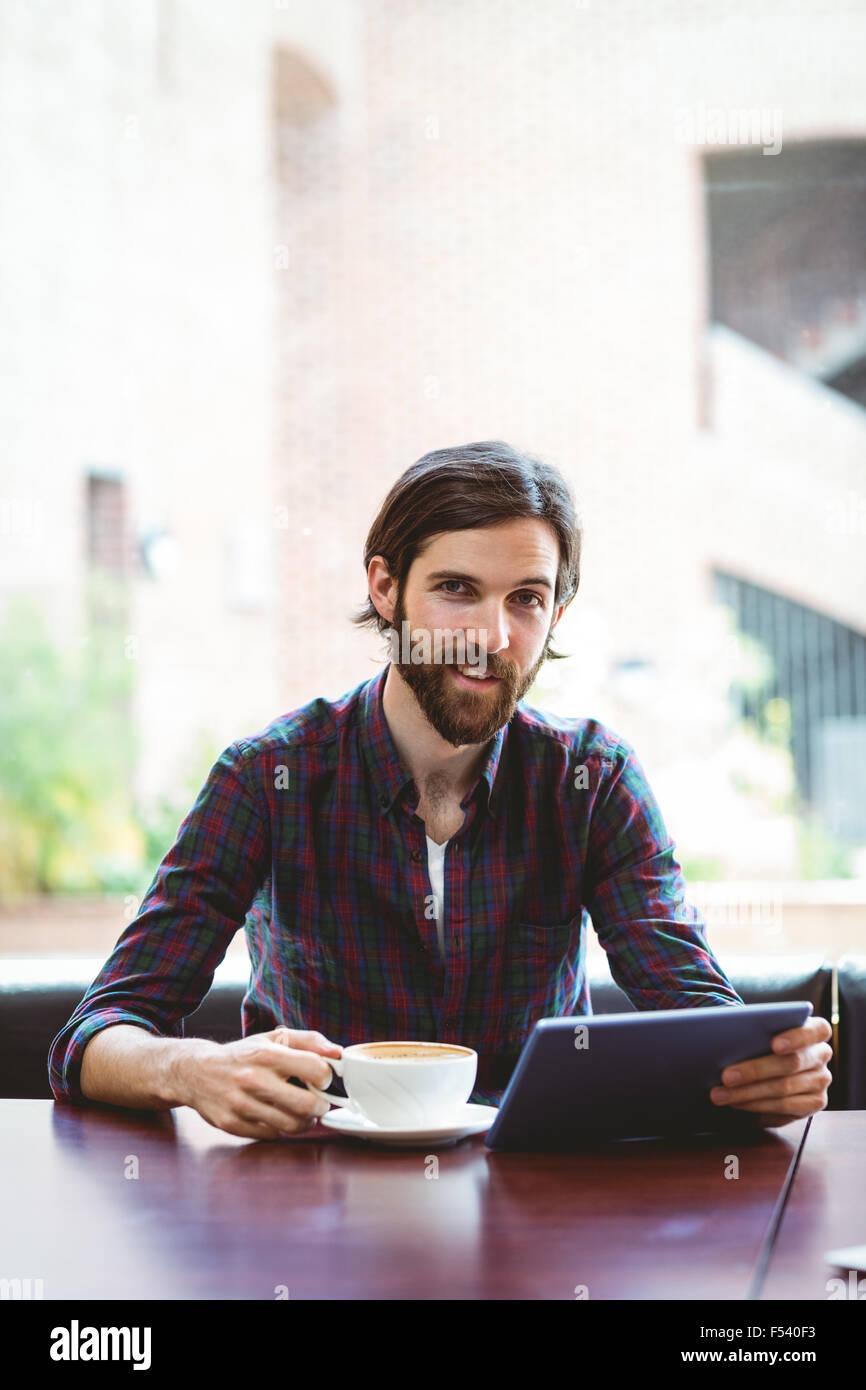 Hipster-Student mit Tablet in Kantine Stockbild