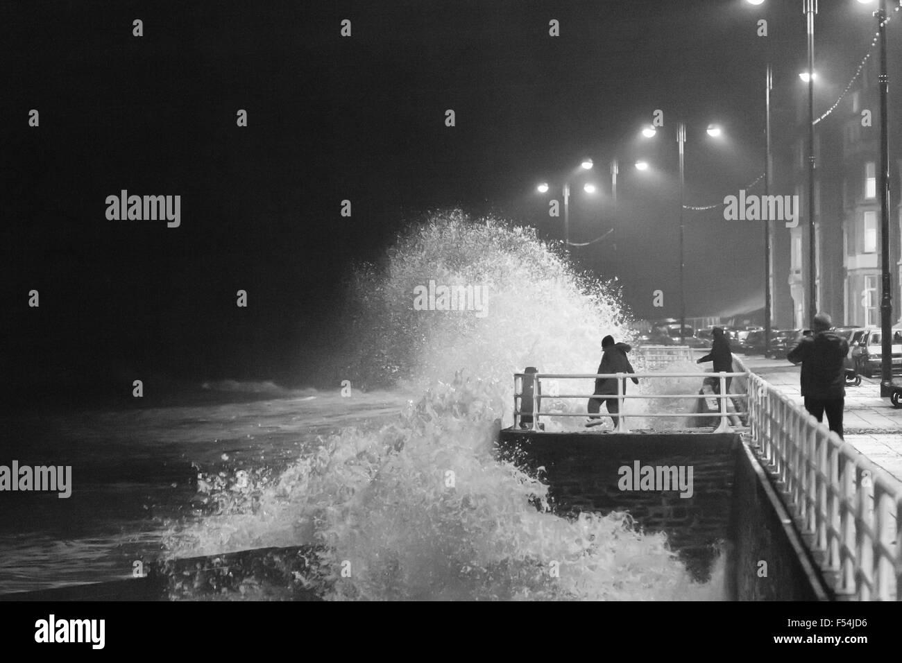 Aberystwyth, Wales, UK. 27. Oktober 2015. Jugendliche nehmen Risiken als die Wellen bei Flut heute Abend Absturz Stockbild