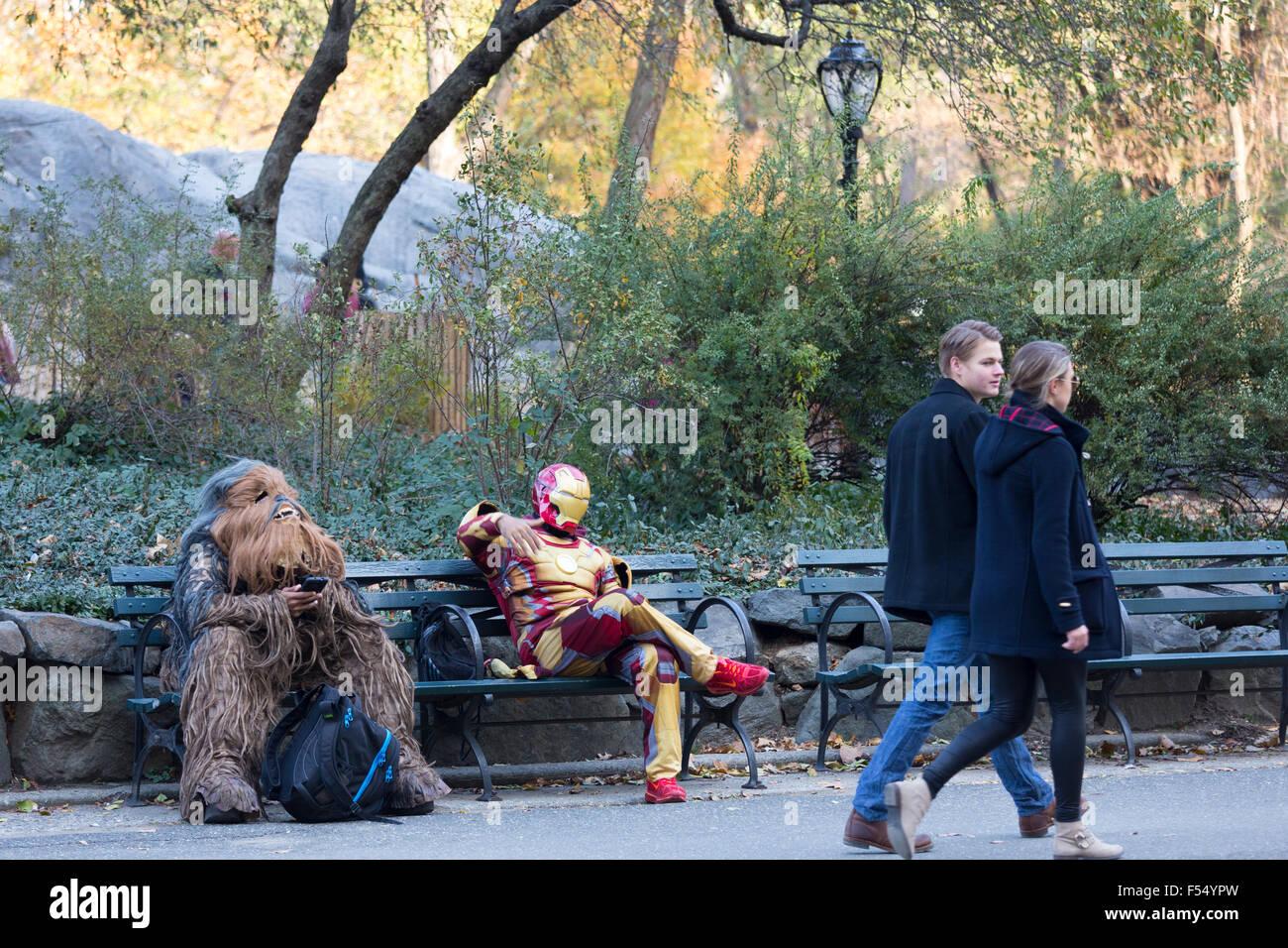 Filmfiguren in Kostüm chillen auf der Parkbank, als Paar im Winter im Central Park, New York, USA vorbeigehen Stockbild
