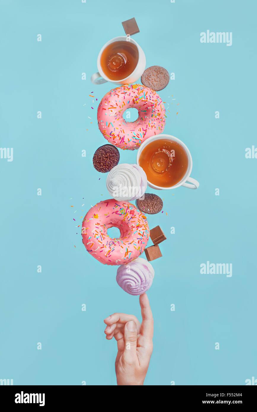 Balancieren Donuts. Glasierte Donuts, Teetassen, Marshmallows und Schokolade-Chips, balancieren auf der Fingerspitze Stockbild