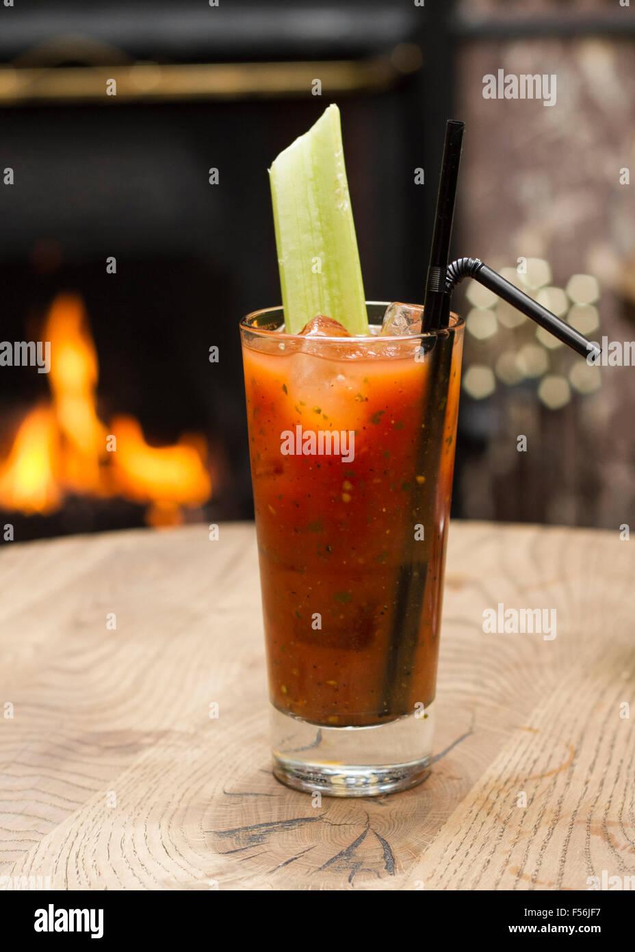 Bloody Mary Cocktail mit einer Selleriestange vor einem offenen Kamin Stockbild