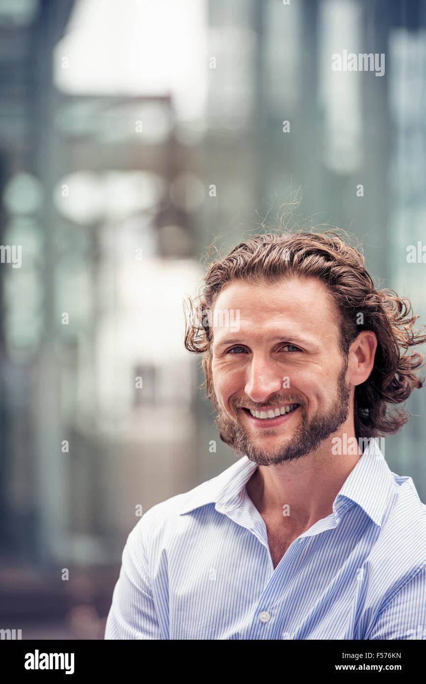 Ein Mann mit lockigem Haar und Bart auf einer Stadtstraße. Stockbild