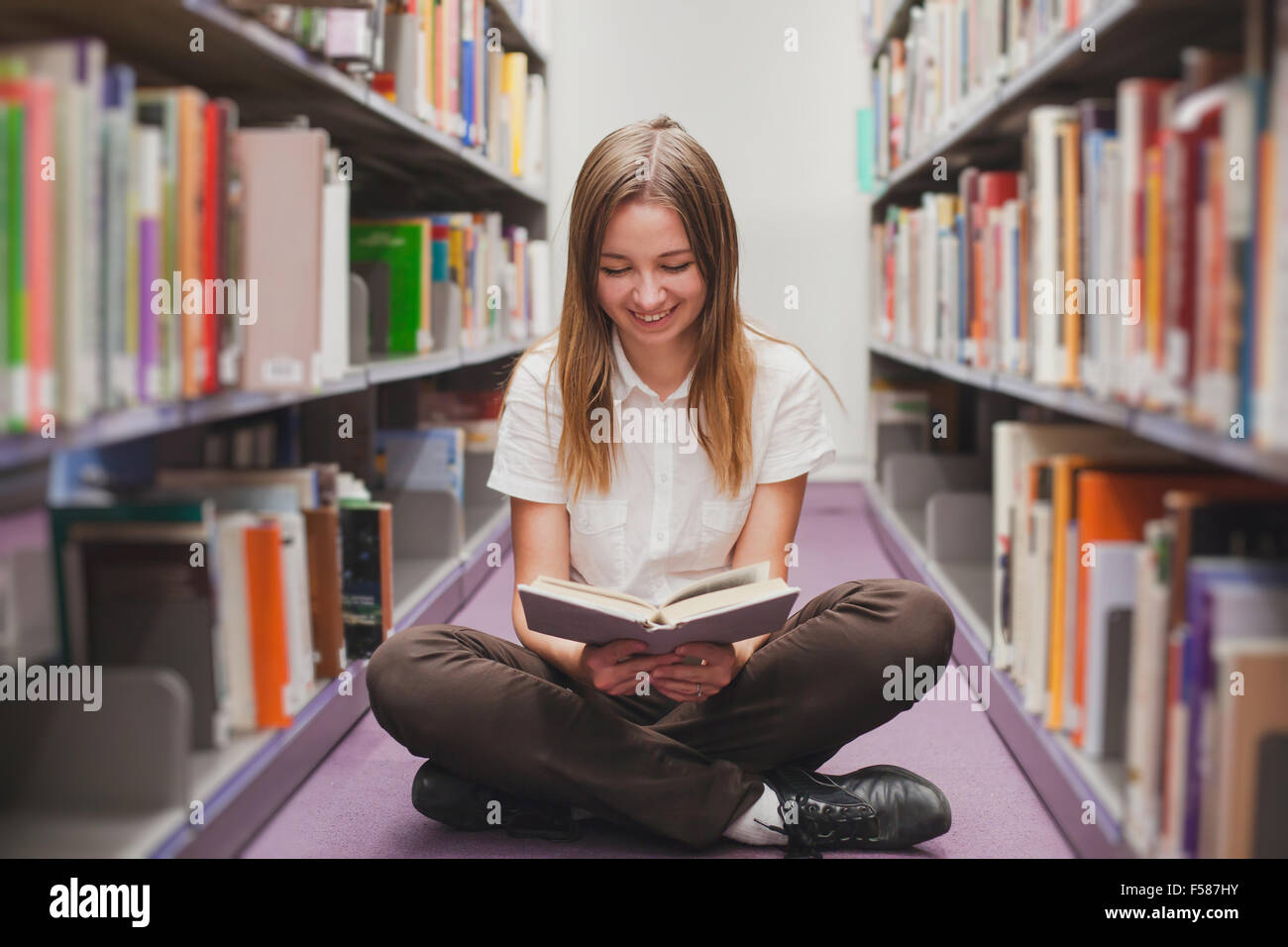 Mädchen lesen in der Bibliothek, lächelt glücklich student Stockbild