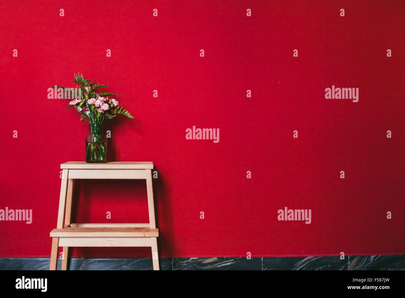 schlichtes Design, Interieur, Blumen in Vase auf der roten Wand Hintergrund Stockbild