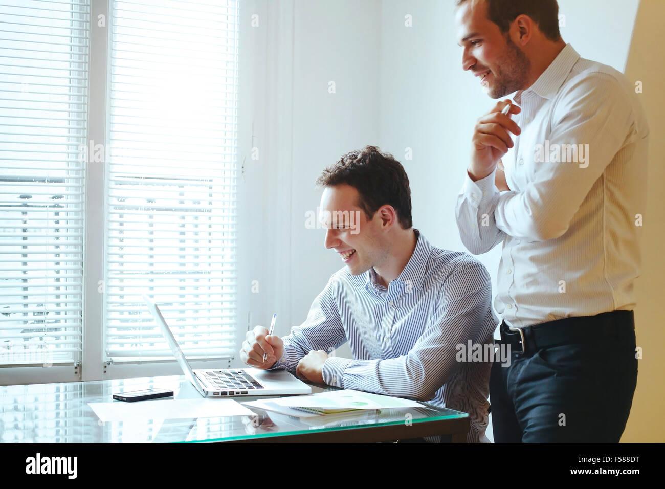 zwei junge Geschäftsleute, die lachend vor computer Stockbild