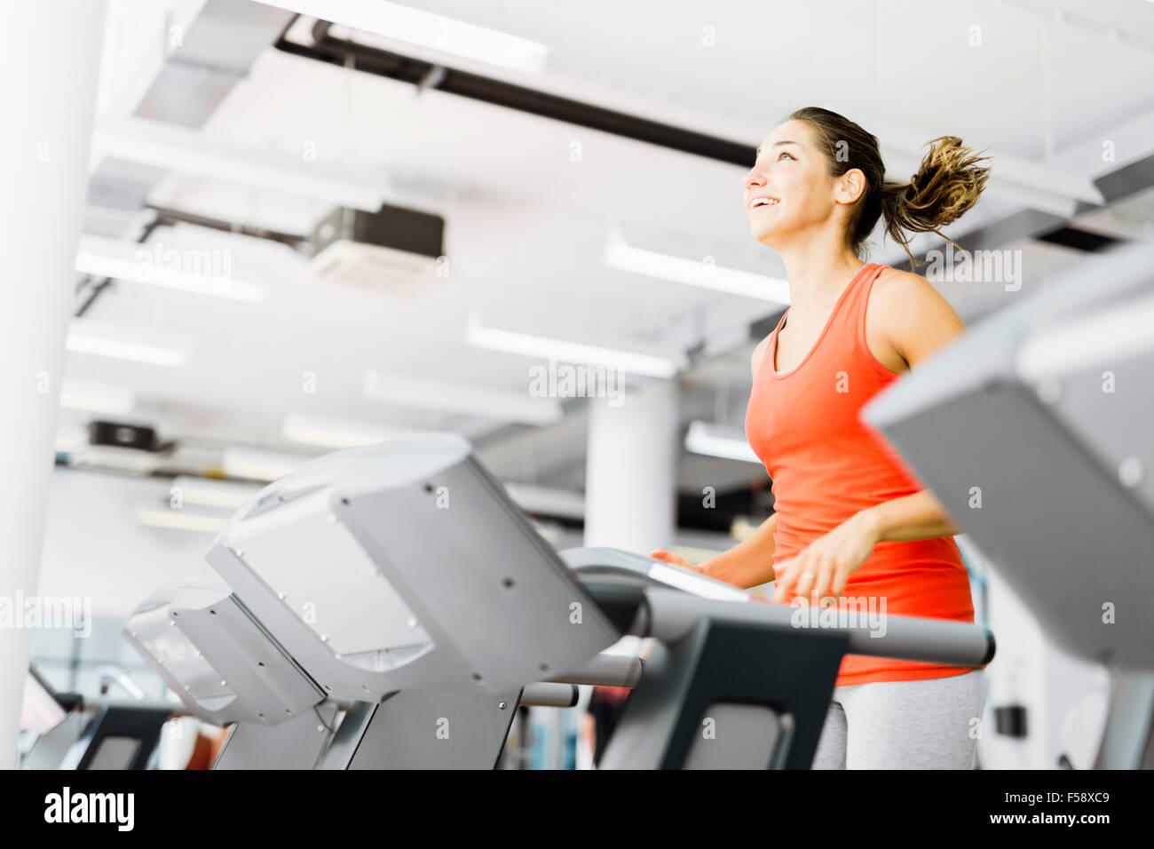 Schöne junge Frau laufen auf einem Laufband im Fitnessstudio und lächelnd Stockbild