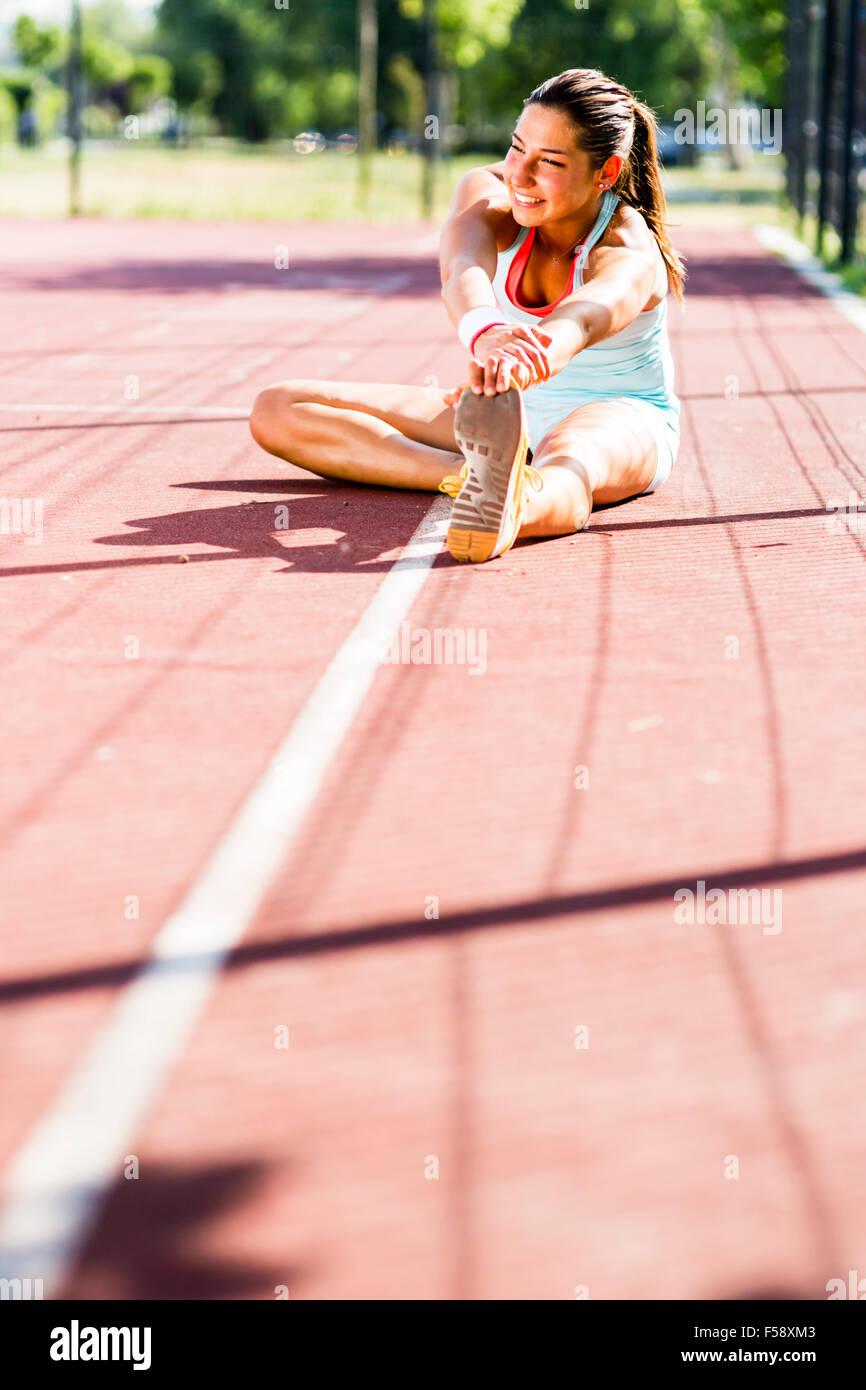 Schöne junge sportliche Frau erstreckt sich im Sommer vor der Ausführung Stockfoto