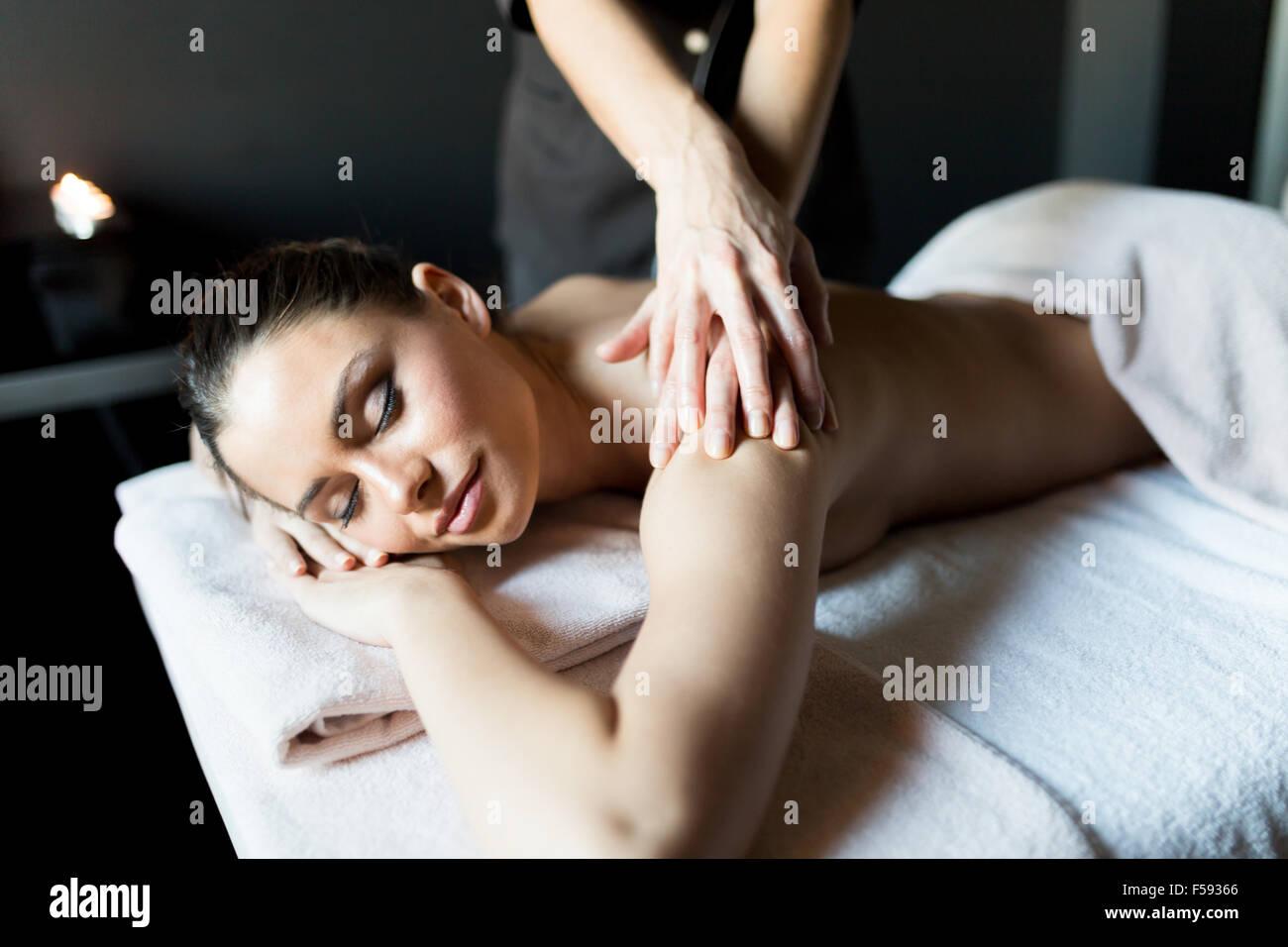 Schöne, junge und gesunde Frau, die ihre Schulter und Körper massiert durch einen professionellen Masseur Stockbild