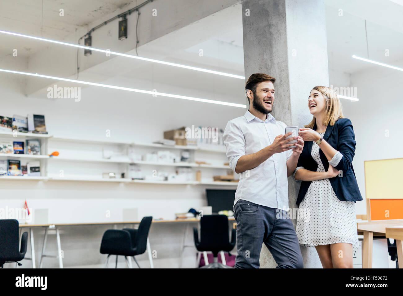 Zwei Kollegen, die mit einem Lachen in einem Büro nach Blick auf den Telefon-Inhalt Stockfoto