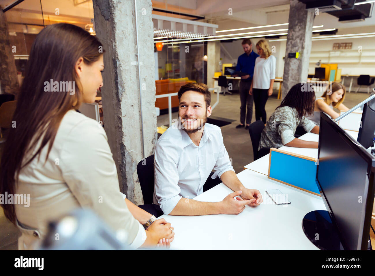 Mitarbeiter bei anstrengenden modernen Büro vor dem Computer Stockbild