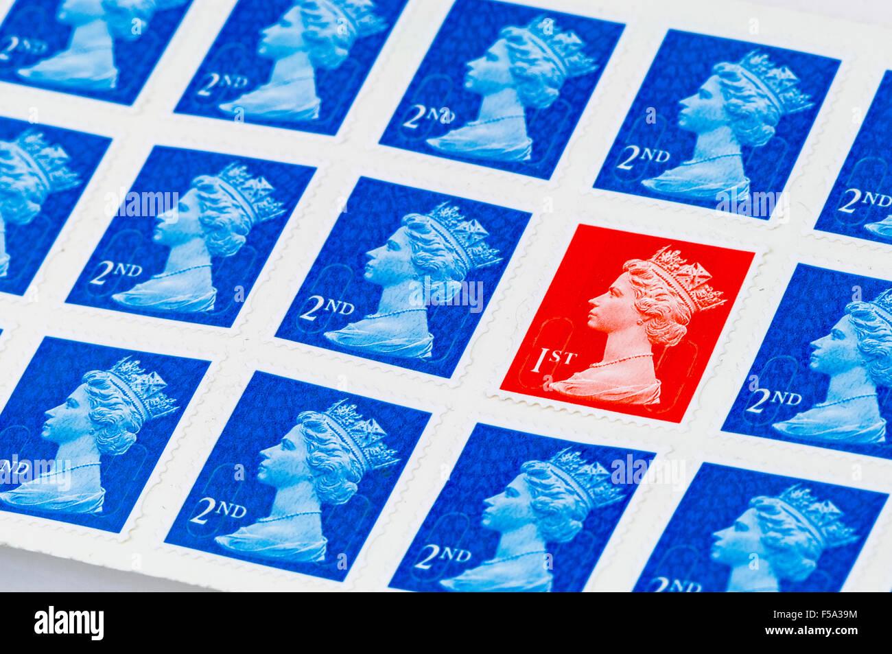 Eine erste 1. Klasse Royal Mail Stempel unter zweiter 2. Klasse Briefmarken Stockbild
