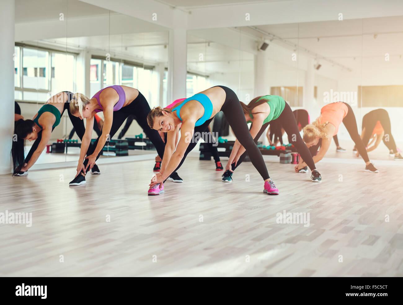 Gruppe von Frauen in bunten Tüchern in einem Fitnessstudio, Aerobic oder Aufwärmen mit Gymnastik und stretching Stockbild
