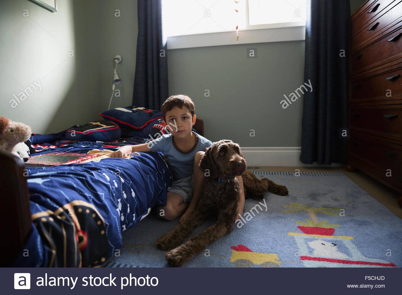 Porträt ernst Knaben mit Hund im Schlafzimmer Stock Stockfoto, Bild ...