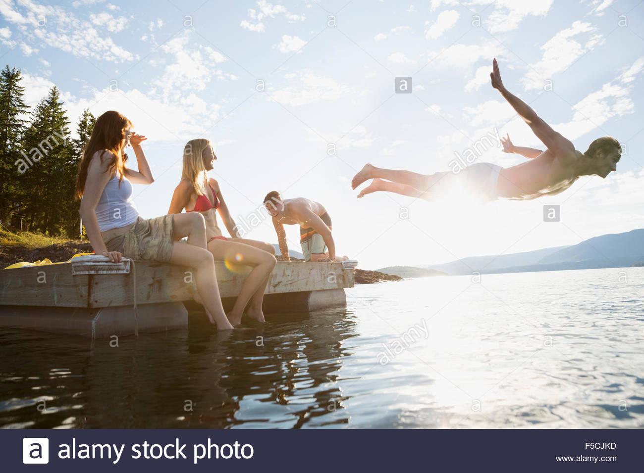 Junge Freunde hängen am sonnigen See dock Stockbild