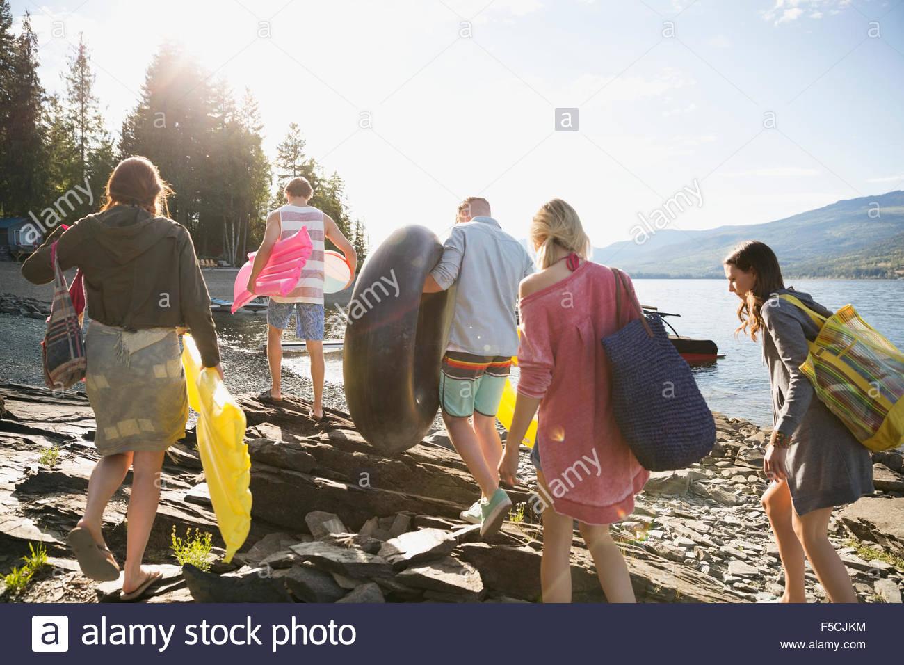 Junge Freunde tragen Pool Flöße am sonnigen Seeufer Stockfoto