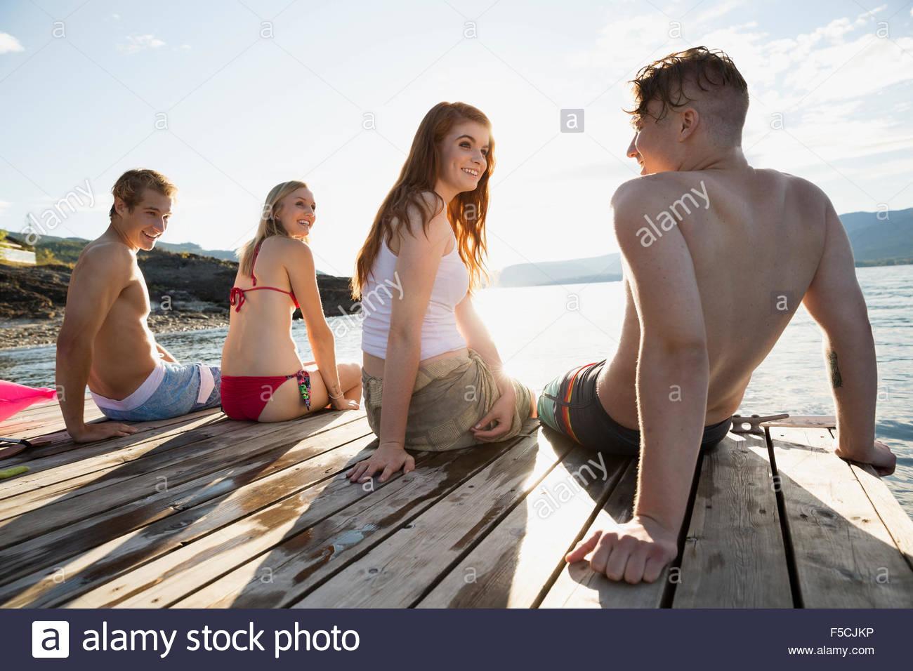 Junge Freunde hängen auf sonnigen See dock Stockbild