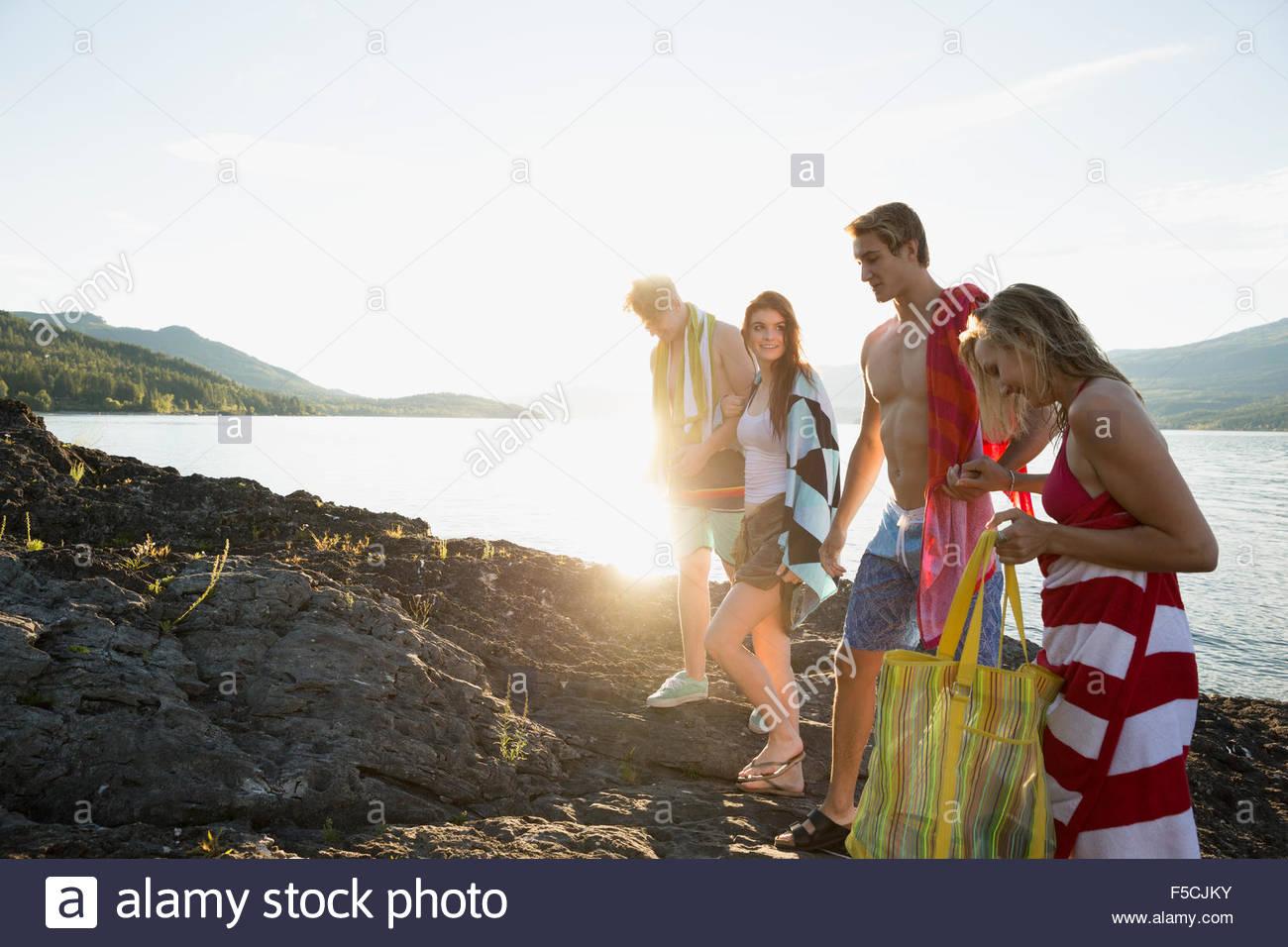 Junge Freunde mit Handtüchern auf den Felsen am See Stockfoto