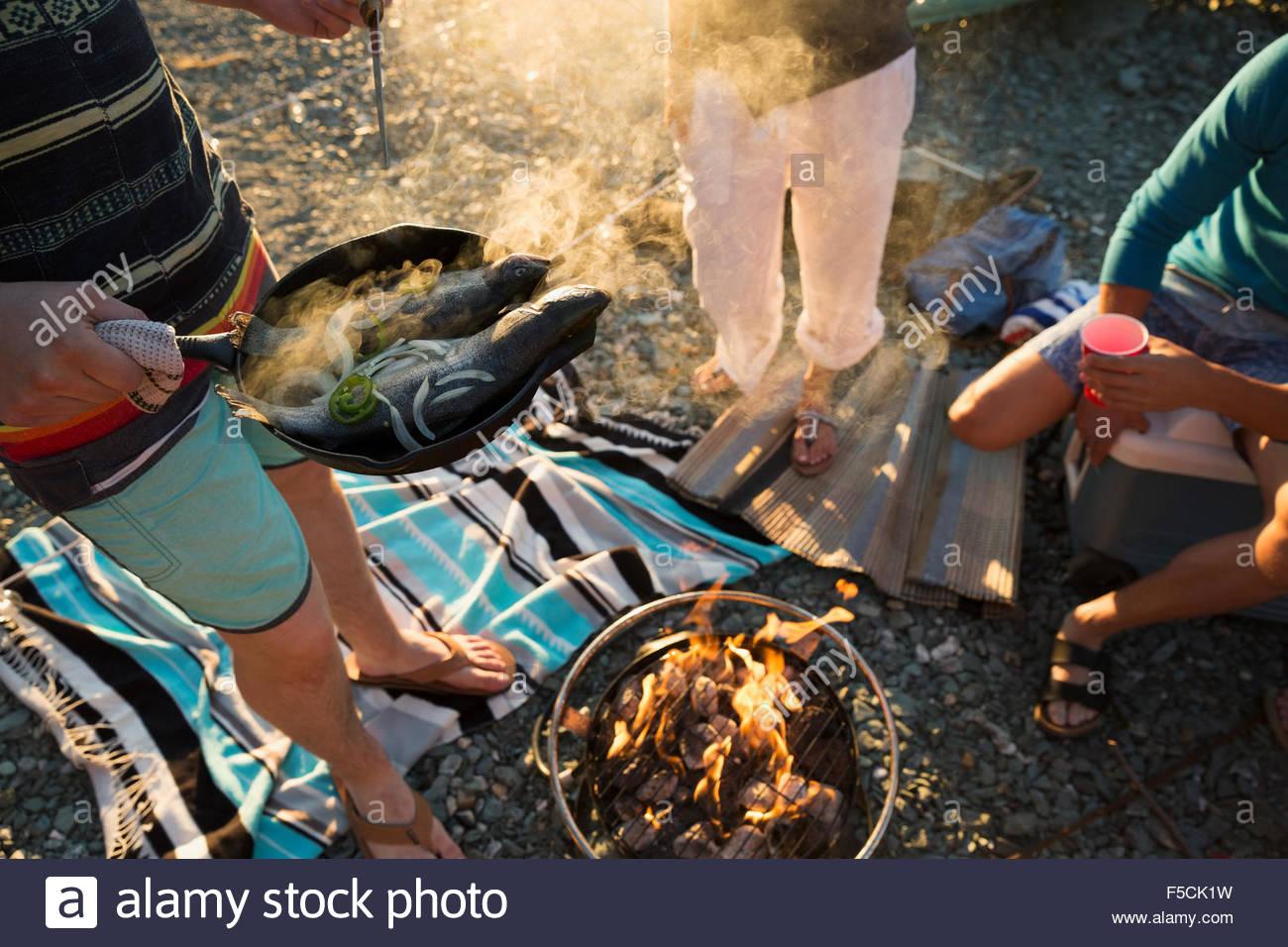 Junge Freunde kochen am Lagerfeuer Stockbild